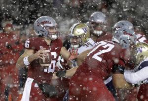 Washington State quarterback Gardner Minshew, left, struggles under pressure from Washington during