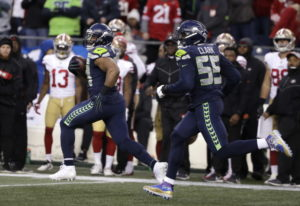 Seattle Seahawks middle linebacker Bobby Wagner, left, runs with defensive end Frank Clark (55) afte
