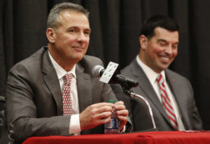 Ohio State NCAA college football head coach Urban Meyer, left, answers questions during a news confe