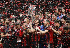 Atlanta United team captain Michael Parkhurst (3) kisses the trophy as teammates celebrate during th