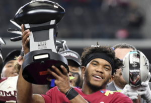 Oklahoma quarterback Kyler Murray hoists the Most Outstanding Player trophy after beating Texas 39-2