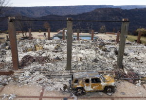 FILE - In this Dec. 3, 2018 file photo, a vehicle rests in front of a home leveled by the Camp Fire