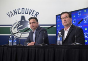Vancouver Canucks head coach Travis Green, left, and general manager Jim Benning and other officials