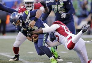 Seattle Seahawks quarterback Russell Wilson, left, is sacked by Arizona Cardinals' Chandler Jones, r
