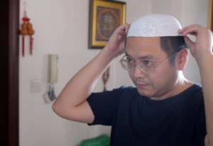 Muslim Chinese poet Cui Haoxin dons an Islamic hat in his home in the city of Jinan in the eastern p