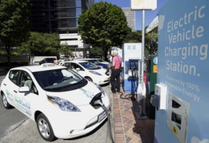 A line of electric cars and newly installed charging stations in front of the Portland General Elect