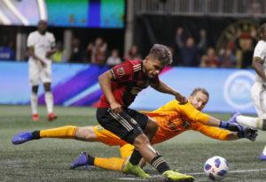 Atlanta United forward Josef Martinez (7) beats Portland Timbers goalkeeper Jeff Attinella (1) to sc