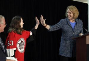 Seattle Mayor Jenny Durkan, right, high-five's Washington Wild hockey team wing Jaina Goscinski, 11,