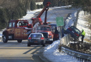 A car is pulled over the barrier after it went down the embankment due to patches of black ice on Ea