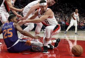 Phoenix Suns forward Mikal Bridges, left, and Portland Trail Blazers guard Seth Curry, right, battle