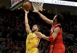 Golden State Warriors guard Klay Thompson, left, drives to the basket on Portland Trail Blazers guar