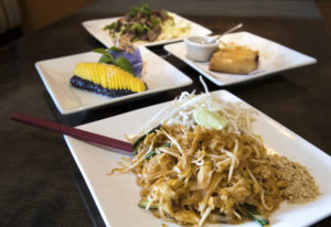 The pad thai with chicken, clockwise from front, fresh mango and ice cream dessert, beef salad and c