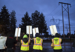 Supporters of the Vancouver Association of Education Support Professionals line the road during a De