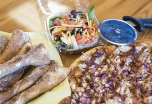 Cinnamon sugar sticks, from left, the garden salad and a Half & Half Signature Pizza combination