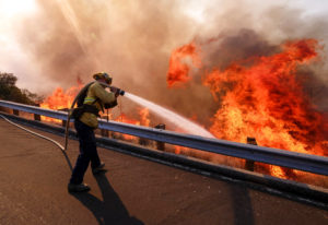 In this Nov. 12, 2018 file photo a firefighter battles a fire along the Ronald Reagan Freeway, aka s