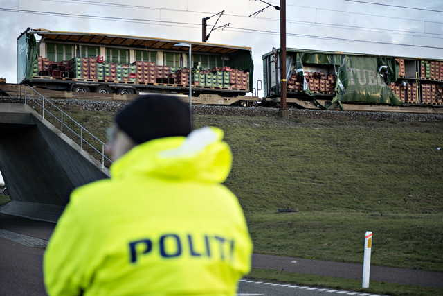 A police officer looks on near a damaged cargo train compartment near the Storebaelt bridge near Ny