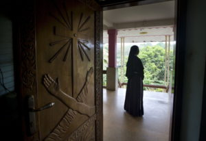 A Catholic nun stands at the foyer of the St. Francis Mission Home in Kuravilangad in the southern I