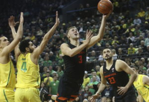 Oregon State's Tres Tinkle, center, goes up to shoot between Oregon's Paul White, left, Ehab Amin an