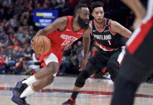 Houston Rockets guard James Harden, left, dribbles past Portland Trail Blazers guard Evan Turner dur