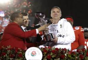 Ohio State coach Urban Meyer, right, holds the trophy after the team's 28-23 win over Washingto