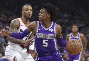 Sacramento Kings guard De'Aaron Fox, right, drives against Portland Trail Blazers guard Damian